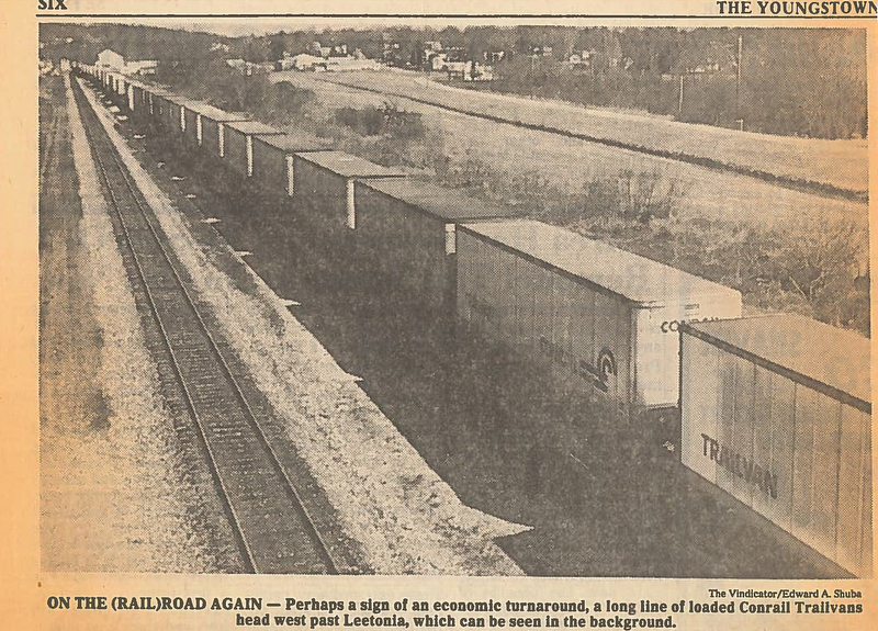 "ONE THE (RAIL)ROAD AGAIN - Perhaps a sign of an economic turnaround, a long line of loaded Conrail Trailvans head west past Leetonia, which can be seen in the background...Photo by Edward A. Shuba - The Vindicator...THE LONG HAUL - Consolidated Rail Corp. (Conrail), formed by the government from the old Penn Central and five other bankrupt carriers, recorded profit of $97.2 million in the second quarter, after posting similar black ink in all of 1982 and 1981.  A key factor in boosting Conrail and the rail industry's resurgence is the continuing growth of so-called""piggyback"" travel, under which railroad flatcars carry already-packed containers.  Aug 14-83...Economic recovery on the road. Loaded trailvans going west. Leetonia in background...Photo taken April 4, 1983...Photo by Edward A. Shuba - The Vindicator"