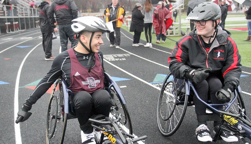 Seated athletes Micah Beckwith, left, of Boardman and Jake Hostetter of Canfield share a moment at the finish of the 100-meter dash on Tuesday at Boardman. Beckwith won the event with a time of 30.2 seconds.