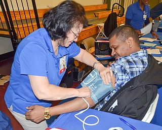 "Mirta Arrowsmith, left, a RN from Mercy Community Health, takes Frank Salas' blood pressure at the ""Citywide Baby Shower"" at the Eugenia Atkinson Recreational Center Saturday, April 7, 2018.  Salas attended the event with his daughters, Lizette Salas, 14, and Lisa Salas, 17, who is expecting a baby.