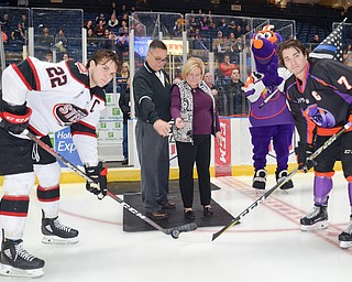 David and Patricia Leo, center, parents of fallen Girard, Ohio Police Officer Justin Leo drop the ceremonial first puck at the Youngstown Phantoms vs. Chicago Steel hockey game at Covelli Centre on Saturday April 7, 2018.  A portion of the night's ticket revenue was donated towards a fund in Justin's name.  Representing Chicago is #22, Matteo Pietroniro, left, and for the Phantoms is #7, Eric Esposito.