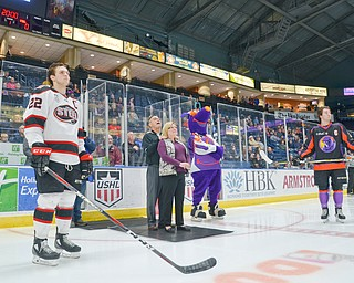 David and Patricia Leo, center, parents of fallen Girard, Ohio Police Officer Justin Leo watch an emotional video about their son prior to dropping the ceremonial first puck at the Youngstown Phantoms vs. Chicago Steel hockey game at Covelli Centre on Saturday April 7, 2018.  A portion of the night's ticket revenue was donated towards a fund in Justin's name.  Representing Chicago is #22, Matteo Pietroniro, left, and for the Phantoms is #7, Eric Esposito.