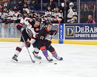 Chicago Steel #26, Aaro Vidgren, fights Youngstown Phantom #17, Joey Abate, for the puck, tripping him and landing himself in the penalty box at the Youngstown Phantoms vs. Chicago Steel hockey game at Covelli Centre on Saturday April 7, 2018.