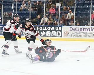 Youngstown Phantom #17, Joey Abate, goes for a ride on the ice after being tripped by Chicago Steel #26, Aaro Vidgren, as Chicago Steel #25, Samuel Bucek, watches on at the Youngstown Phantoms vs. Chicago Steel hockey game at Covelli Centre on Saturday April 7, 2018.
