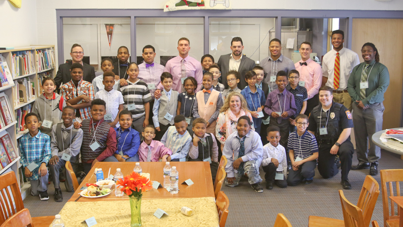 """A group of Youngstown State University men come to Williamson Elementary School on Youngstown's South Side twice monthly for a """"gentlemen's"""" meet and lunch event with male students. The idea is to provide positive male role models for young boys and teach them proper etiquette."""