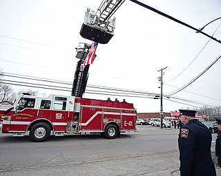 WEATHERSFIELD, OHIO - APRIL 9, 2018: A Weathersfield fire truck transporting Weathersfield Township Fire Chief Randall Pugh's casket passes under the American flag after the conclusion of his funeral, Monday morning. DAVID DERMER | THE VINDICATOR