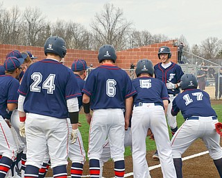 Austintown Fitch's #14, Nick Belcik, is about to be pummeled by his teammates after hitting a grand-slam against Columbiana at the home opener of the new Richard L. Coppola Field in Austintown on Thursday, April 12, 2018.