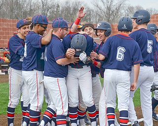 Austintown Fitch's #14, Nick Belcik, (center) is pummeled by his teammates after hitting a grand-slam against Columbiana at the home opener of the new Richard L. Coppola Field in Austintown on Thursday, April 12, 2018.