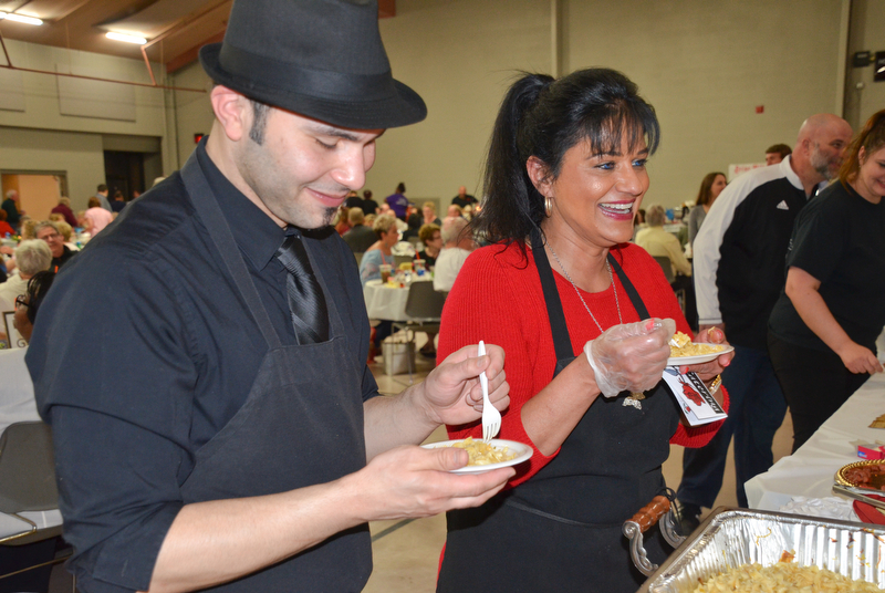 "Angel Febres, left, and Theresa Tanferno, two employees from the Selah Restaurant in Struthers, sample haluski from Monica's Catering at the annual ""Taste of Struthers"" event held at St. Nicholas in Struthers on Thursday April 12, 2018.