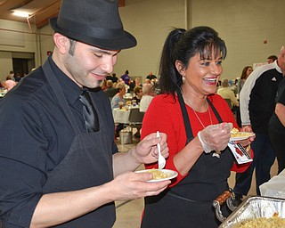 """Angel Febres, left, and Theresa Tanferno, two employees from the Selah Restaurant in Struthers, sample haluski from Monica's Catering at the annual """"Taste of Struthers"""" event held at St. Nicholas in Struthers on Thursday April 12, 2018.  Photo by Scott Williams - The Vindicator"""