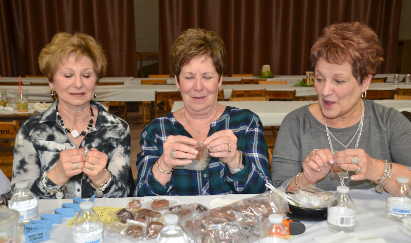 "Three friends from Struthers, from left to right, Sandy Beckwith, Judy Davenport, and Judy Takach, race one other to see who can open their sample chocolate from Giannios Candy first at the annual ""Taste of Struthers"" event held at St. Nicholas in Struthers on Thursday April 12, 2018.