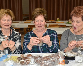"""Three friends from Struthers, from left to right, Sandy Beckwith, Judy Davenport, and Judy Takach, race one other to see who can open their sample chocolate from Giannios Candy first at the annual """"Taste of Struthers"""" event held at St. Nicholas in Struthers on Thursday April 12, 2018.  Photo by Scott Williams - The Vindicator"""