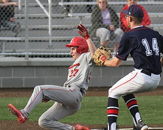 Columbiana's Hunter Znter (27) scores as Fitch's Nick Belcik tries to cover at the plate during 4-12-18 action at Fitch.