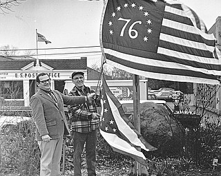"""BICENTENNIAL FLAG - Canfield City officials Friday hoisted two new flags, which will be flown over the Village Green day and night for the duration of the bicentennial celebration.  Left is City Manager Chris Paparodis with Orville Paugh, superintendent of parks and streets.  Regular flags were lowered and the Bennington flag - which has 13 stripes of red and white on a field of blue, 13 stars and numeral """"76,"""" was raised.  Below the American flag is a newly purchased Ohio State Flag.  Photo published April 19, 1975."""