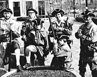 """MUSKETS IN HAND - Members of the newly-organized Mahoning Valley Colonial Brigade, costumed and bearing muskets, paraded through the Youngstown Federal Plaza Saturday in observance of George Washington's """"real"""" birthday.  Participating were Jim Caylor (seated) and (from left standing) Howard F. Sarver, Howard P. Sarver, John Caylor, William J. Sarver Jr. and William J. Sarver Sr.  Photo published February 23, 1975."""