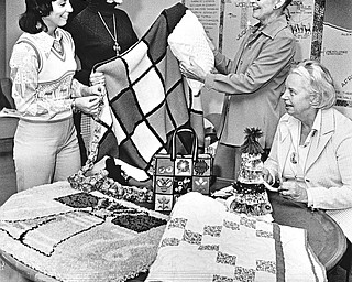ARTISTS WITH NEEDLES - A Liberty Bell hooked rug, colorful afghan, patchwork quilt, needlepoint tote bag, and calico chain and doll are admired by (left to right) Mrs. Robert Anderson, bazaar chairman; Mrs. David Starkey, Mrs. William W. Hanks, chairman of the bicentennial workshop, and Mrs. Steward Hume, chairman of the Women's Association of First Presbyterian Church.  Photo by Paul R. Schell.