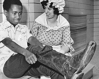 STYLES FROM THE PAST - Darren Boatwright finds it takes some pulling to get into an old-fashioned boot.  Mrs Paul Hunter, Junior League member, wears a dress which might have been in style when such boots were the fashion.  Photo published Saturday, November 1, 1975.  Photo by Paul R. Schell
