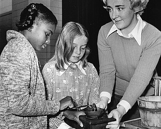 COFFEE MILL - Human energy used to provide the power for grinding.  Trying their hands (left to right) are Sherraine Thomkins and Christine Reisinger with Mrs. J. Walter Dragelevich of the Junior League providing instruction.  Photo published Saturday, November 1, 1975.  Photo by Paul R. Schell.