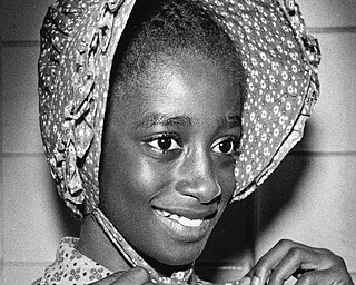 Patricia Mattison, fifth grader, tries a bonnet from the collection when it made a recent visit to Mary Haddow School.  Photo published Saturday, November 1, 1975.  Photo by Paul R. Schell.