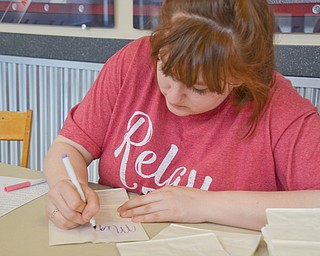 Maddie Sanders, a YSU Junior, early childhood education major, writes the names of those who are battling cancer and those who have passed away from cancer on paper bags for the Luminaria Ceremony at Relay for Life at Beeghly Center on the campus of Youngstown State University on Saturday April 14, 2018.