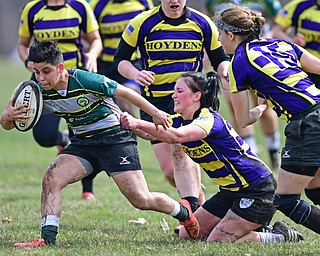 YOUNGSTOWN, OHIO - APRIL 14, 2018: Elaina Ruiz, green, runs with the ball while being tackled from behind by a defender during a rugby match, Saturday morning in Youngstown. DAVID DERMER | THE VINDICATOR