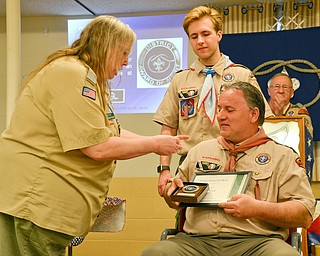 Beth Harnishfeger, left, presents John Russell, seated, with the District Award of Merit at the Whispering Pines Boy Scouts Recognition Dinner at St. James Episcopal Church in Boardman on Sunday, April 15, 2018.  Russell's son, Colin, watches on in approval. The award is available to registered Scouters who render service of an outstanding nature at the district level.  Photo by Scott Williams - The Vindicator