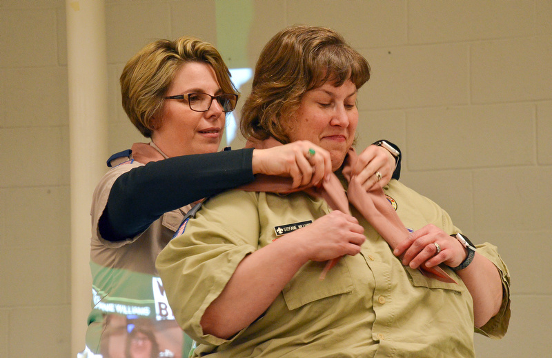 Steph Kelly (left) places a neckerchief around Stephanie Williams' neck during the Wood Badge Ceremony at the Whispering Pines Boy Scouts Recognition Dinner at St. James Episcopal Church in Boardman on Sunday, April 15, 2018. 