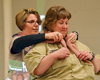 Steph Kelly (left) places a neckerchief around Stephanie Williams' neck during the Wood Badge Ceremony at the Whispering Pines Boy Scouts Recognition Dinner at St. James Episcopal Church in Boardman on Sunday, April 15, 2018.   Photo by Scott Williams - The Vindicator