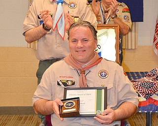 John Russell, seated, is applauded by his son Colin, left, and Bill Moss, district training chairman, after receiving the District Award of Merit at the Whispering Pines Boy Scouts Recognition Dinner at St. James Episcopal Church in Boardman on Sunday, April 15, 2018. The award is available to registered Scouters who render service of an outstanding nature at the district level.  Photo by Scott Williams - The Vindicator