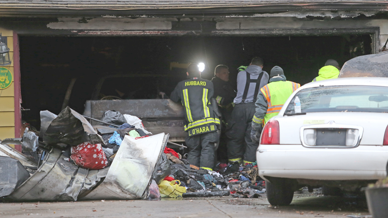 Firefighters and Ohio State Fire Marshals sort through the remains of the gutted garage in the 400 block of Simler Street in Hubbard on Nov. 22. James Vint died of smoke inhalation after becoming trapped in the garage. There is still no cause for how the fire started.