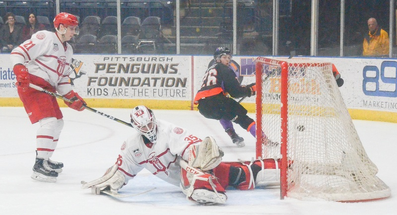 Phantoms penalty killer Matthew Barry looks back to see the puck in the net behind Fighting Saints goaltender Cole Weaver during Saturday's USHL playoff game at the Covelli Centre. Trailing is Saints forward Alex Steeves. Youngstown won, 3-2.