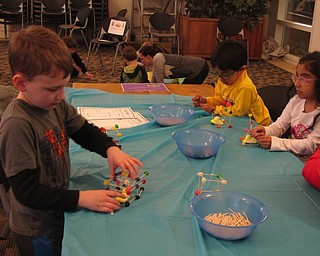 """Neighbors   Zack Shively.The Austintown library had a """"Marshmallow Peep Science"""" program on March 14, which included seven different stations relating to Peep candies, such as the building station pictured. Children used toothpicks and jellybeans create structures around Peeps."""