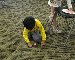 Neighbors   Zack Shively.The children tried each of the stations at the Austintown library's Marshmallow Peep Science program, and they went to their favorite stations during the end of the program. Pictured, the children used a catapult to launch Peeps into Easter baskets.