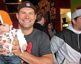 William D. Lewis The Vindicator Haden Holmes, 13 weeks, meets former Browns player Joe Thomas, at left  NFL star John Greco during draft night event at Suzies Dogs and Drafts in Boardman. Haden is a son of Matt and Samantha Holmes of Austintown.