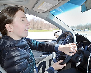 Hayley Ward, 17, from Mars, PA, bites her lip as she gives Vindicator photographer Scott Williams and reporter Graig Graziosi a ride for their lives around a fast pace skid control exercise at a TireRack.com Street Survival School event at Boardman Park on Sunday, April 29, 2018. 