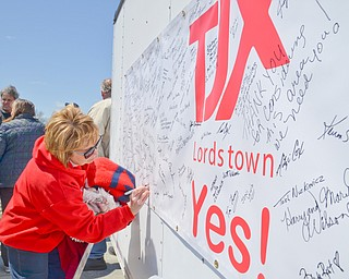 Melodie Montgomery, from Lordstown, signs her name to a banner in support of TJX at a rally to keep TJX in the Mahoning Valley on Sunday, April 29, 2018 at the Lordstown High School track.  
