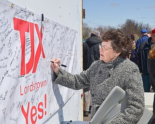 Anna Strickland signs her name to a banner in support of TJX at a rally to keep TJX in the Mahoning Valley on Sunday, April 29, 2018 at the Lordstown High School track.  