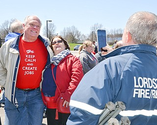 Eric Wishart, right, takes a photo of Angela Wishart with Lordstown Mayor Arno Hill at a rally to keep TJX in the Mahoning Valley on Sunday, April 29, 2018 at the Lordstown High School track.  