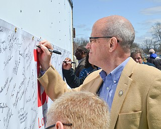 Ohio State Representative Michael J. O'Brien signs his name to a banner in support of TJX at a rally to keep TJX in the Mahoning Valley on Sunday, April 29, 2018 at the Lordstown High School track.  