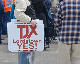 Dan Crouse, from Warren, (left) passes out pro TJX yard signs to attendees at a rally to keep TJX in the Mahoning Valley on Sunday, April 29, 2018 at the Lordstown High School track. 