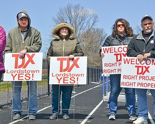 From left to right, Chris Lee, his mother Evelyn Lee, Jennifer Lackey, and Brian Ripple, all of Lordstown, hold signs in favor of TJX at a rally to keep TJX in the Mahoning Valley on Sunday, April 29, 2018 at the Lordstown High School track.  