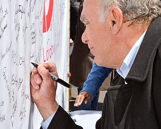 Trumbull County Commissioner Frank S. Fuda signs his name to a banner in support of TJX at a rally to keep TJX in the Mahoning Valley on Sunday, April 29, 2018 at the Lordstown High School track. 