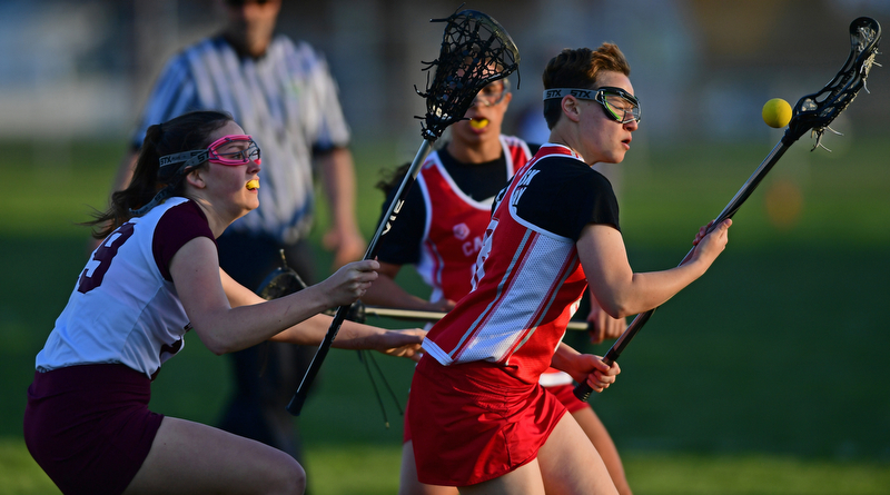 BOARDMAN, OHIO - APRIL 30, 2018: Canfield's Oliva Vandevender looks the ball into her stick while being pressured by Boardman's Colleen Yambar during the first half of their game on Monday night at Spartan Stadium. DAVID DERMER | THE VINDICATOR
