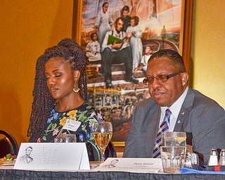 Arielle Green, left, and her father Jeff Green bow their heads in prayer at the Mahoning County Republican Party's Annual Abraham Lincoln Day Dinner held at The Maronite Center on Tuesday, May 1, 2018.  Looming in the background is local artist Ray Simon's painting of Abraham Lincoln, which is a permanent fixture at the Abraham Lincoln Presidential Library.     Photo by Scott Williams - The Vindicator