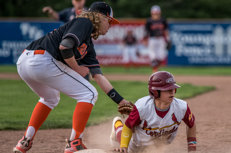 THE VINDICATOR | DIANNA OATRIDGEÊ Cardinal Mooney's Ethan Shaw avoids a pick off attempt by Howland's Dylan Keller during their Division II Sectional Final match-up at Cene Park on Wednesday. The Cardinals won the game 11-2.