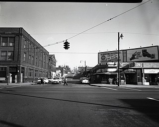 "89.119 B1aF323 N. View looking North-East along Watt St. from E. Federal St., Boardman Hotel, Super Poultry- Hot Dogs and Coca Cola sign, St. Cyril's Church and School. 1960. Archives, original negative is 4"" x 5"" black and white. Digital image is 800 dpi RGB."