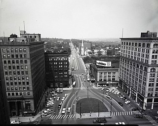 "89.119 B1F285 N.  View looking North-East along the Square and Wick Avenue from atop the Mahoning National Bank Building. Left- Dollar Bank, Union Bank, Brown's Drug Store. Right- People's Bank, Palace Theatre, Household Finance Corp., Palace Grill, Palace Hotel, First Presbyterian Church, Masonic Temple.June 3, 1961. Archives, original negative is 4"" x 5"" black and white. Digital image is 800 dpi RGB."
