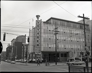 "89.119 B3F157 Negative of the Voyager Motor Inn at the intersection of Market Street and Front Street in downtown Youngstown. Multiple directional signs are present on the telephone poles on either side of the corner. The Tod Hotel sits on the left side of the Voyager. The railing for the Market Street Bridge is visible in the bottom right corner. Taken July 1965. Archives, original negative is 4"" x 5"" black and white. Digital image is 800 dpi RGB."