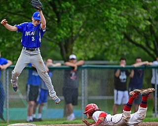 STRUTHERS, OHIO - MAY 15, 2018: Poland's Alex Barth jumps to catch the ball while Niles' Nick Guarnieri steals third base in the third inning of their OHSAA tournament game on Tuesday afternoon at Cene Park. Niles won 4-3. DAVID DERMER | THE VINDICATOR