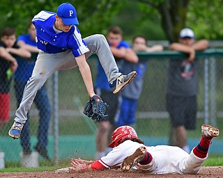 STRUTHERS, OHIO - MAY 15, 2018: Poland's Alex Barth reaches in a unsuccessful attempt to tag out Niles' Nick Guarnieri as he steals third base in the third inning of their OHSAA tournament game on Tuesday afternoon at Cene Park. Niles won 4-3. DAVID DERMER | THE VINDICATOR