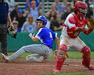 STRUTHERS, OHIO - MAY 15, 2018: Poland's Braeden O'Shaughnessy slides across home plate to score a run behind Niles catcher Nick Guarnieri in the seventh inning of their OHSAA tournament game on Tuesday afternoon at Cene Park. Niles won 4-3. DAVID DERMER | THE VINDICATOR
